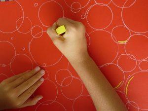 cercles blancs fond rouge enfant main pastel